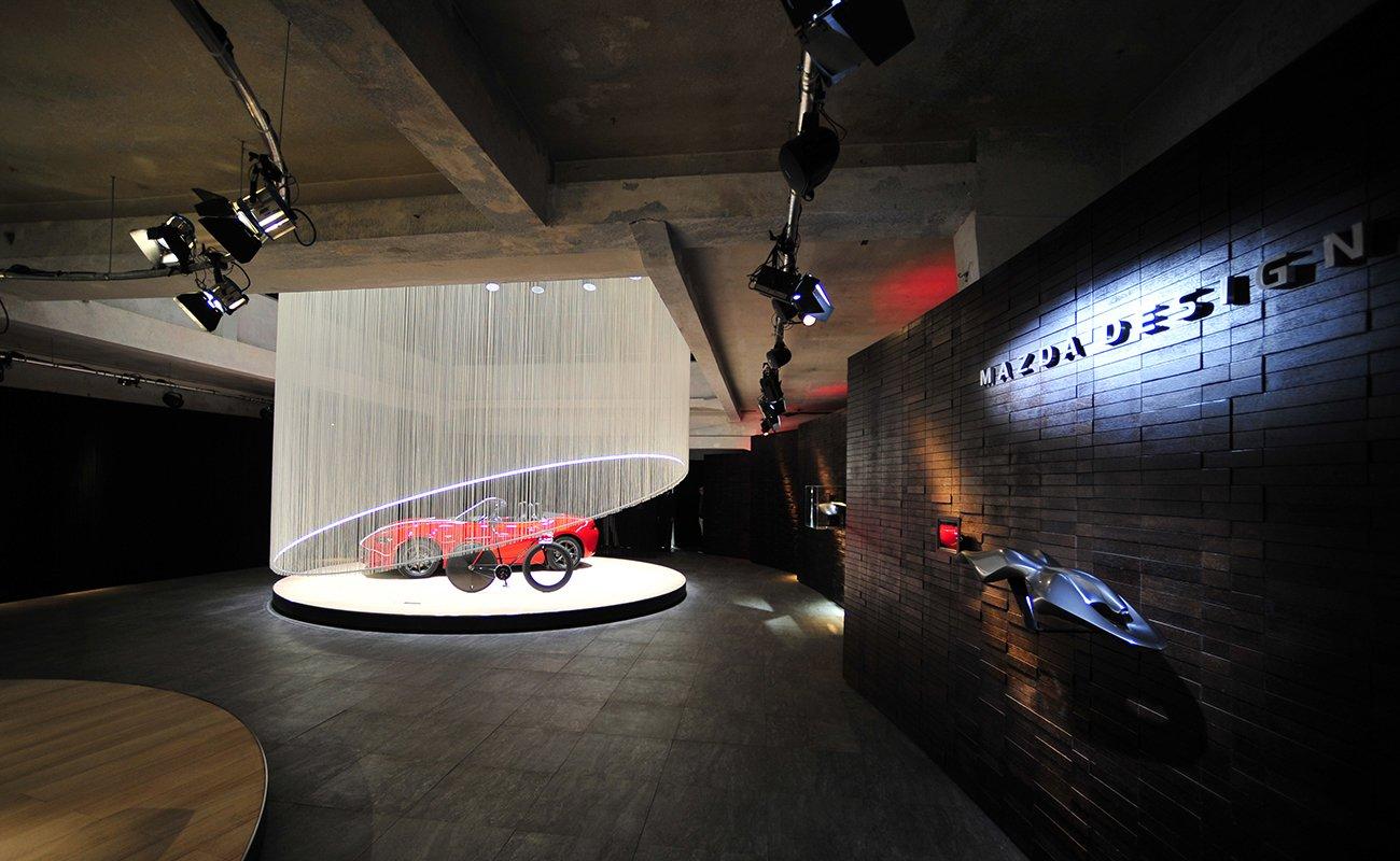 Vista della pedana di esposizione prodotto e parete in wengè con il logo Mazda Design