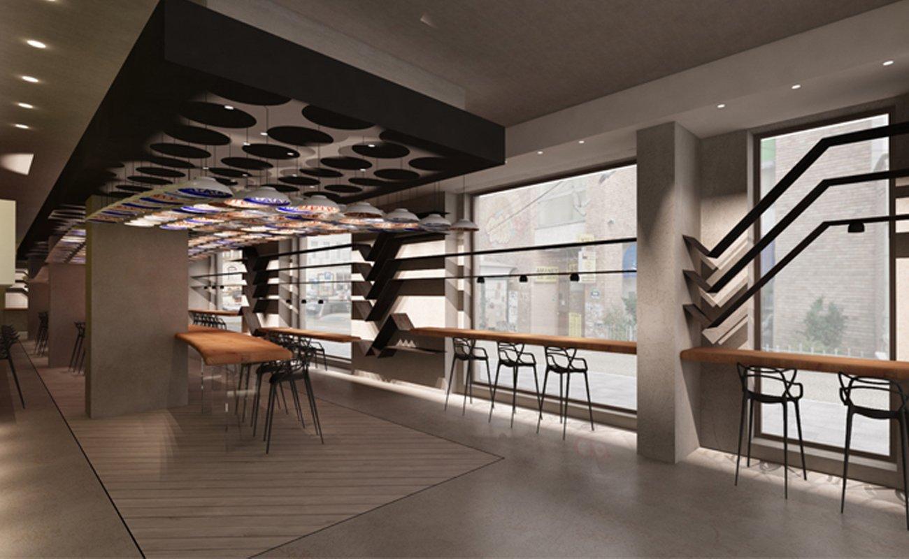 Zona consumo con tavoli alti e sgabelli di fronte alla vetrata
